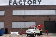 Channel letters being installed on a building reading Factory